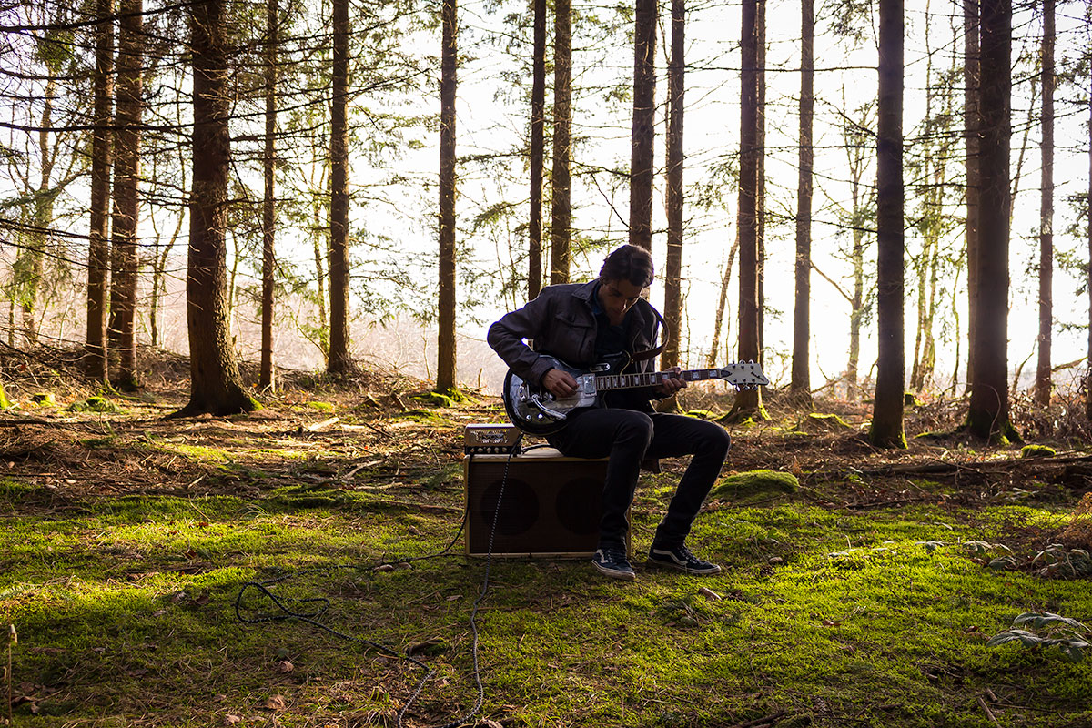Photo of Psychedelic Indie Rock Music Artist Samuel Christen, full body photo in nature playing guitar